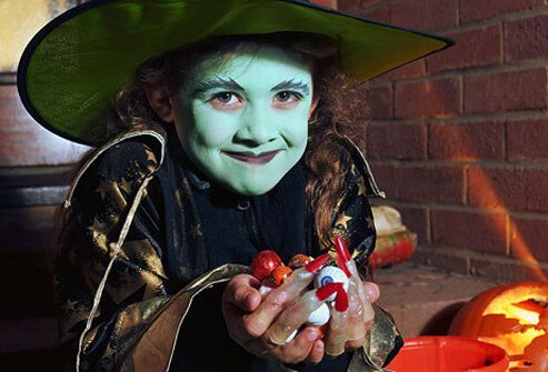 Girl in 'witch' halloween costume, holding sweets