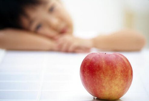 Photo of child looking at apple.