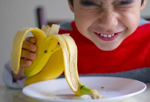 Photo of boy eating a banana.