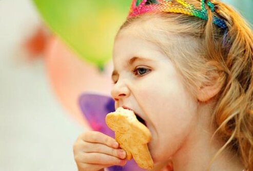 Photo of girl eating cookie.