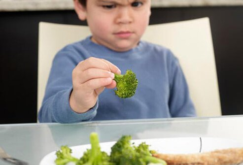 Photo of boy frowning at brocolli.