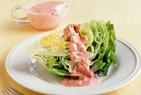 A photo wedge of iceberg lettuce with dressing.
