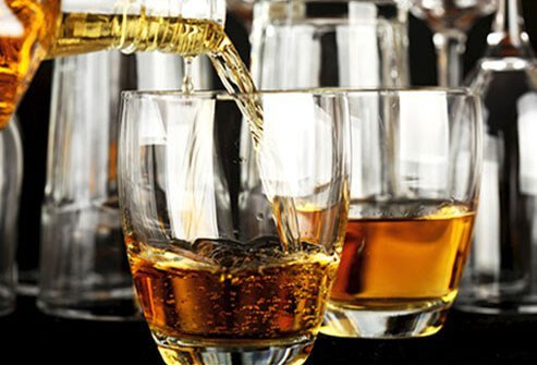 Whiskey being poured into glasses, increasing depression risk.