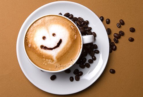 A cup of coffee and coffee beans on a table, helping to fight depression.