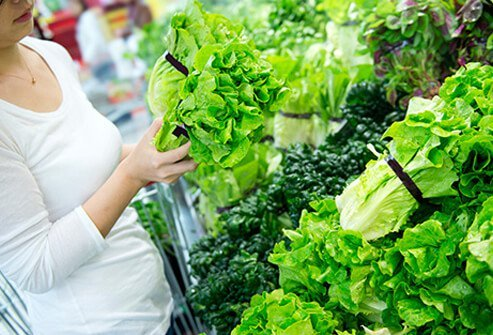 A woman shopping for leafy greens at the supermarket to help fight depression.