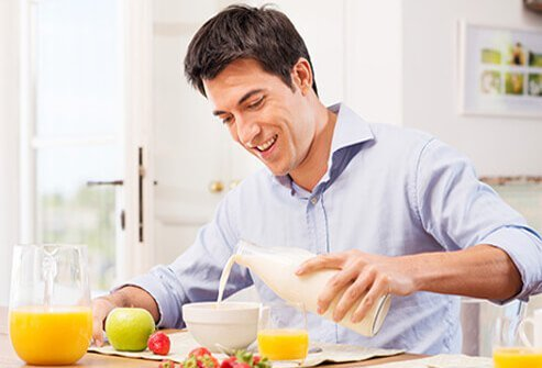 A man pours milk into his breakfast cereal next to a pitcher of orange juice.