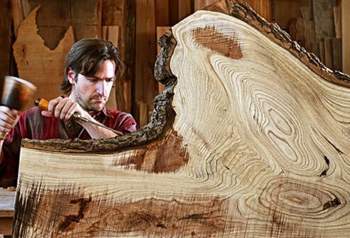 Photo of carpenter chiseling wood.