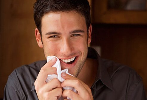 Photo of man wiping mouth on napkin.