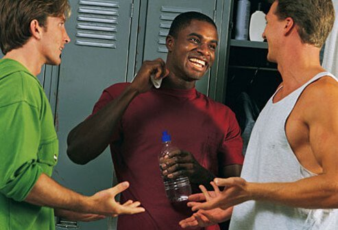 Photo of three young men in a locker room.