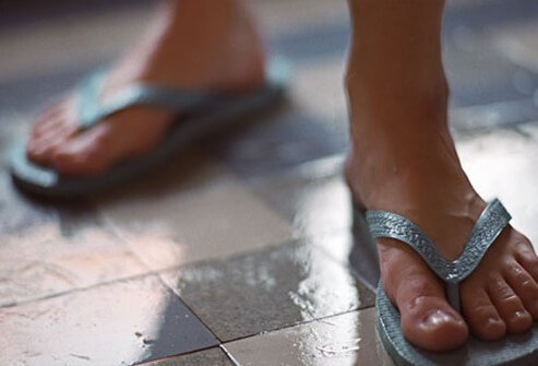 Photo of a person wearing flip flops on the shower floor.