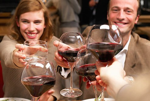 People celebrating drinking glasses of wine.