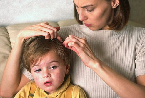 Photo of mother checking child for head lice.