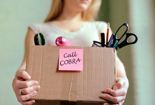 A woman who has been laid off carrying her belongs in a box with a note to call COBRA.