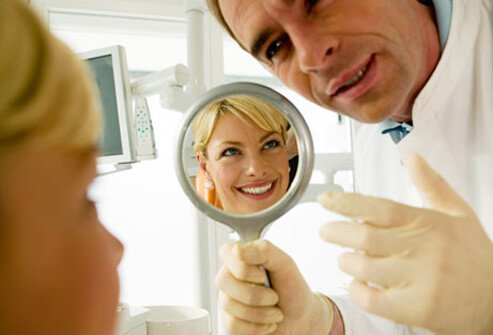 A dentist holds up a mirror for a woman.