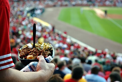 A man carries a tray of food down to his seat at the baseball park.