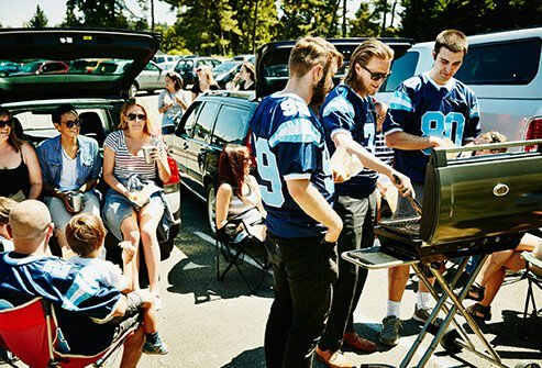 A group of tailgaters serve up hot dogs.