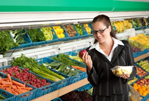 A businesswoman buys a fruit salad at the supermarket.