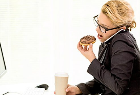 A woman eating a donut at her desk.