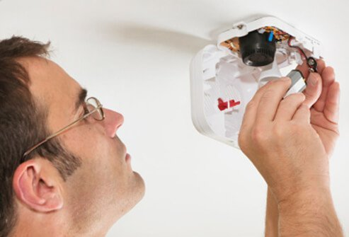 A man changes the battery in a smoke detector.