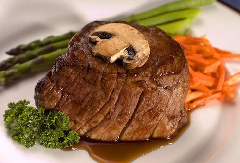 A photo of filet mignon with asparagus and carrots.