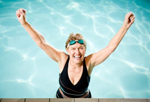 A healthy senior woman with raised arms expresses positive energy in the pool.
