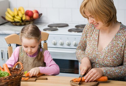 A daughter helps her mother prepare a healthy meal.