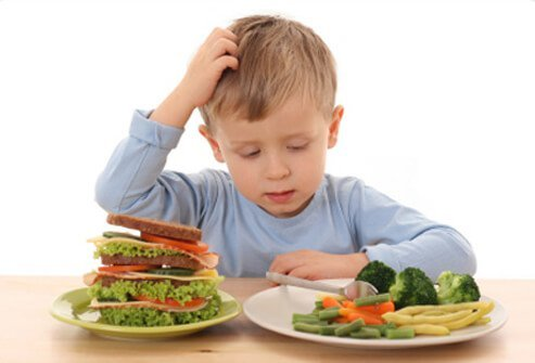 A young boy tries to decide between eating a sandwich and vegetables.