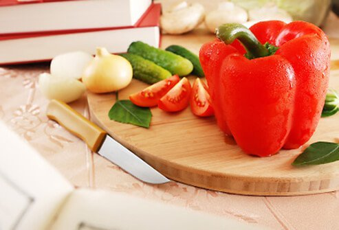A red bell pepper and fresh vegetables on a cutting board.