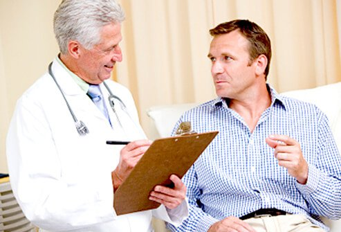 A doctor prepares to examine an elderly patient for hemorrhoids.