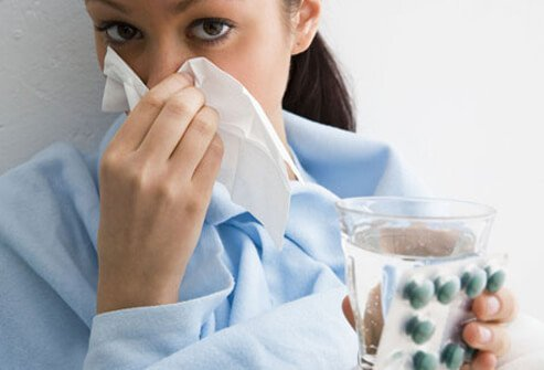 Photo of a sick woman with high blood pressure blowing her nose.