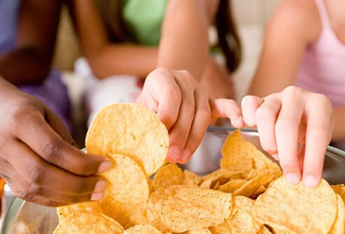 A photo of kids eating chips, at risk for high blood pressure.
