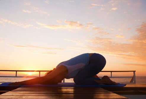 A photo of a woman doing yoga, treating high blood pressure.