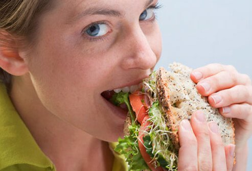 A photo of a woman eating a healthy sandwich, living with high blood pressure.