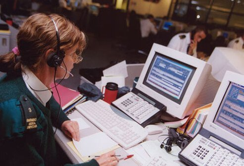 A photo portrays the high stress job of an emergency dispatcher.