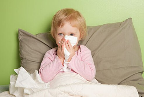 A young girl is sick in bed with a runny nose.