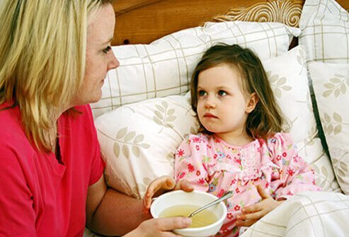 A mom gives a sick child soup in bed.