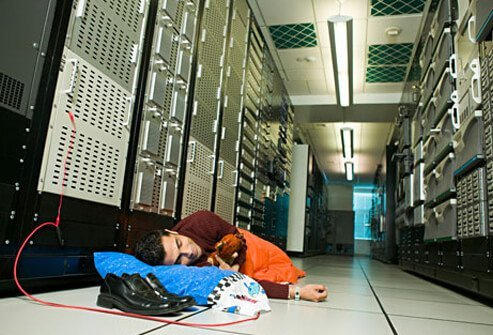 Photo of a network administrator asleep on the floor.