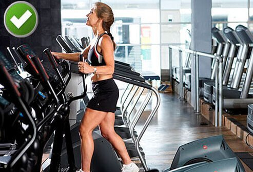 A woman working out on an elliptical machine.