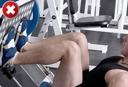 A man doing a leg press with knees bent too deeply.