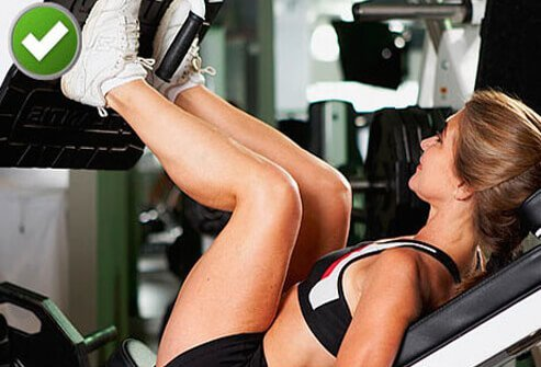 A trainer showing proper position on a leg press.