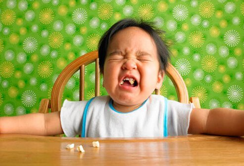 A baby crying in a highchair.