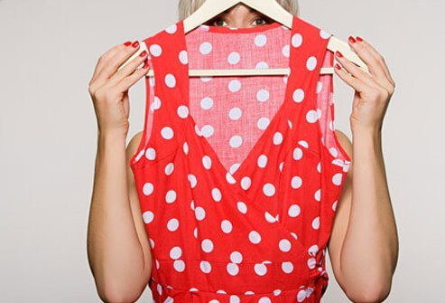 Woman holding a polka dot dress.