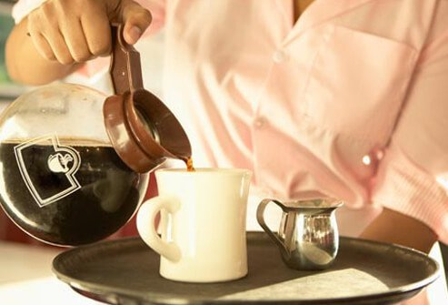 A server pours a cup of coffee.