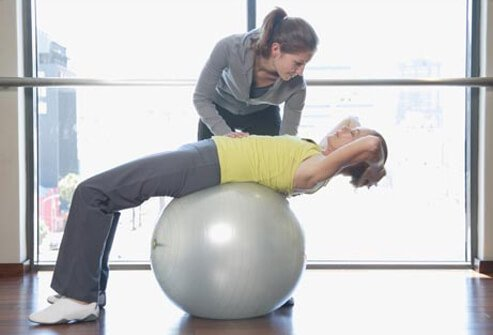 Woman on exercise ball with trainer.