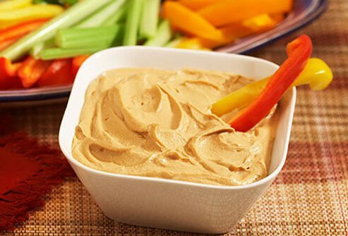 Photo of a bowl of hummus and red bell peppers.