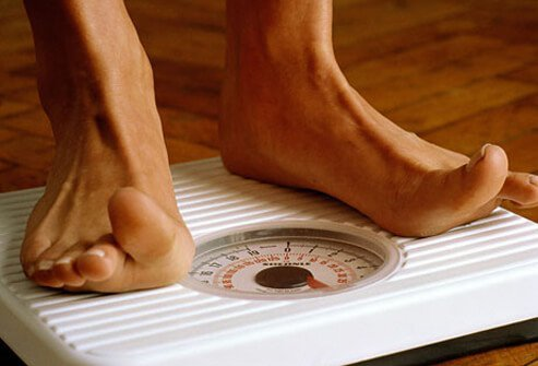 A woman checks her weight on a scale.