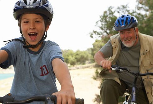 A grandfather and his grandson have fun riding their bikes.