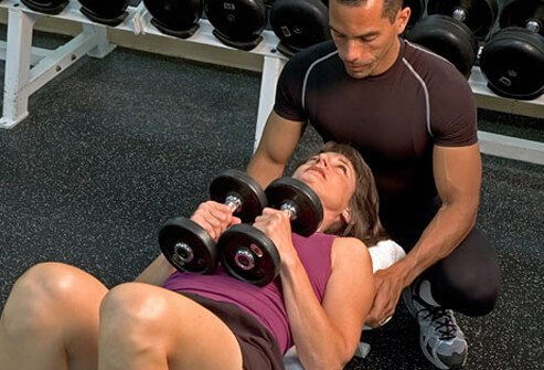 A woman works out with a trainer.