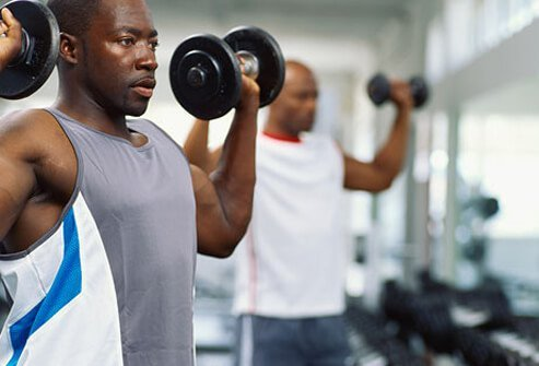 A man lifts weights in the gym.
