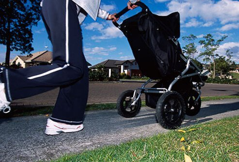 A mother jogs with her child in a stroller.